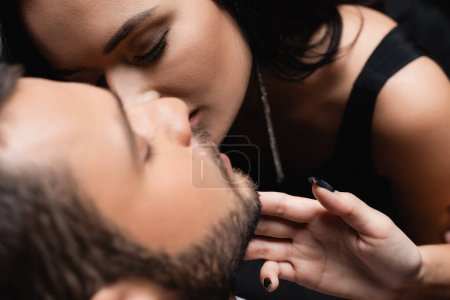 Photo for Passionate woman kissing young man on blurred foreground - Royalty Free Image