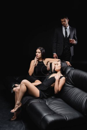 Photo for Businessman with glass of whiskey standing near sexy women sitting on leather couch isolated on black - Royalty Free Image