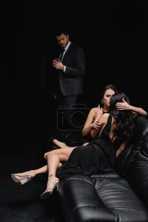 Photo for Seductive women hugging on leather couch near man with glass of whiskey isolated on black - Royalty Free Image