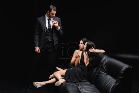 Photo for Man in suit near sexy women embracing on leather couch on black background - Royalty Free Image