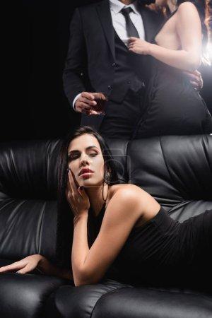 sexy Frau liegt auf Ledercouch in der Nähe Liebhaber umarmen auf schwarzem Hintergrund