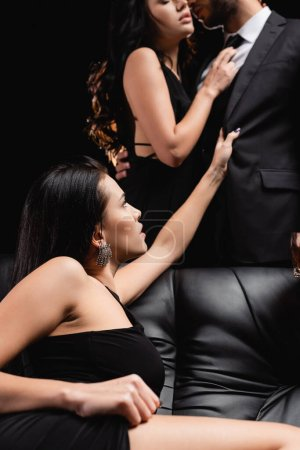 Photo for Passionate woman sitting on leather couch near lovers kissing on blurred background isolated on black - Royalty Free Image