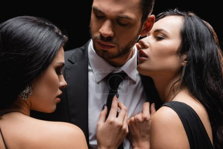 brunette, passionate women near successful businessman isolated on black