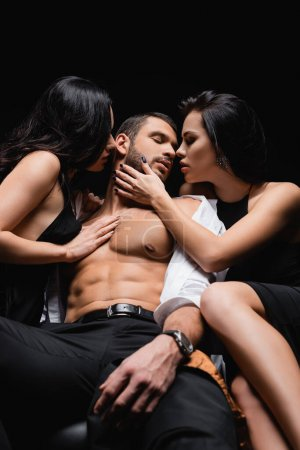 sexy man in unbuttoned shirt sitting on leather couch near passionate women isolated on black