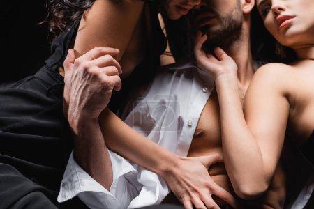 vue partielle de femmes passionnées séduisant jeune homme isolé sur noir