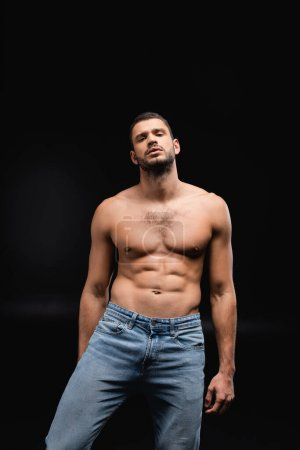 sexy man with muscular torso looking at camera on black background