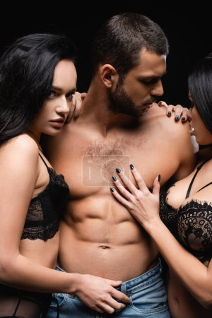 femmes passionnées en lingerie embrassant homme avec torse musculaire isolé sur noir