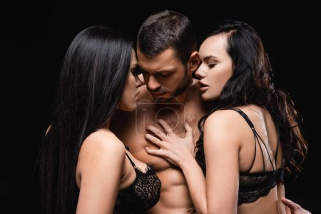 Photo for Sexy man near seductive, brunette women seducing him isolated on black - Royalty Free Image