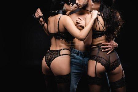 mujeres apasionadas en máscaras faciales cerca de hombre sexy aislado en negro