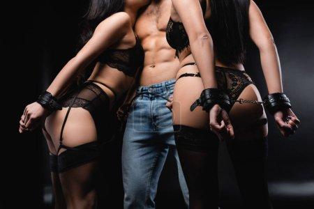vista parcial del hombre sin camisa en jeans sosteniendo látigo azotes cerca de mujeres esposadas en negro