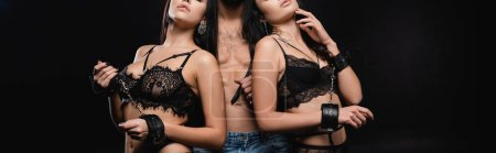 Photo for Partial view of young women in lingerie and handcuffs seducing shirtless man isolated on black, banner - Royalty Free Image