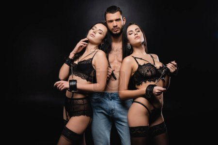 Photo for Sexy man with flogging whip near passionate women in lingerie and handcuffs on black - Royalty Free Image