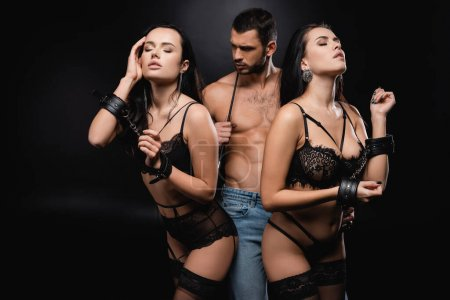 Photo for Young woman in lingerie and handcuffs seducing muscular man with flogging whip on black - Royalty Free Image