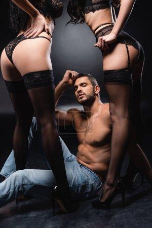 homme torse nu en jeans assis sur le sol près de femmes passionnées sur fond noir