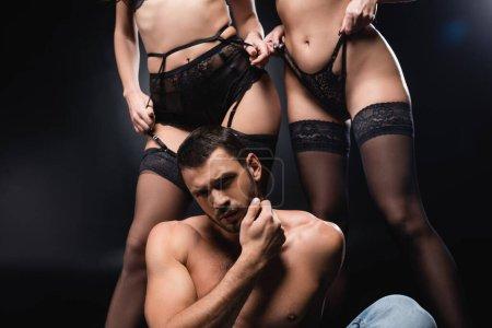 hombre sin camisa tocando la cara mientras está sentado cerca de mujeres sexy en lencería y medias en negro