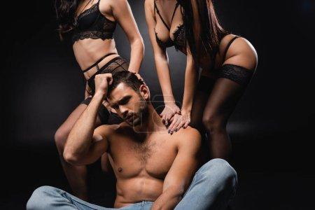 sexy, hombre sin camisa sosteniendo la mano cerca de la cabeza mientras está sentado cerca de mujeres apasionadas en negro