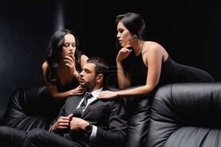 successful businessman sitting on leather couch near sexy women on black