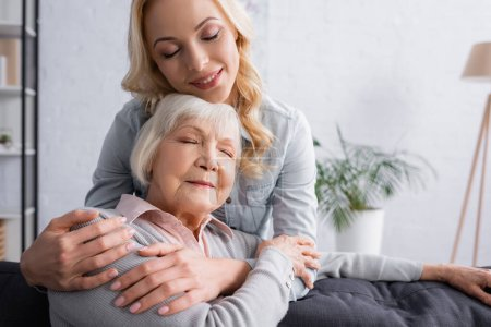 Adult woman smiling and hugging grey haired mother