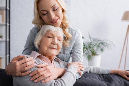 Femme adulte souriante et étreignant mère aux cheveux gris