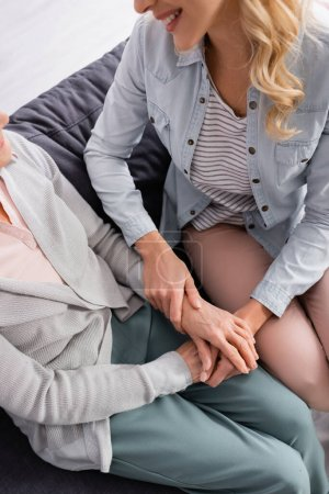 Cropped view of smiling woman touching hands of senior mother