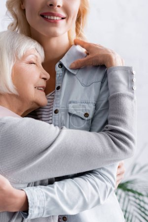 Photo for Happy grey haired woman hugging smiling daughter - Royalty Free Image