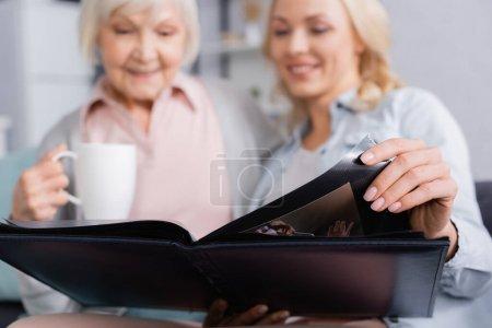 Photo pour Album photo entre les mains d'une femme floue près de la mère avec une tasse - image libre de droit