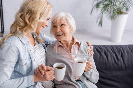 Photo pour Femme souriante avec thé étreignant mère aînée à la maison - image libre de droit