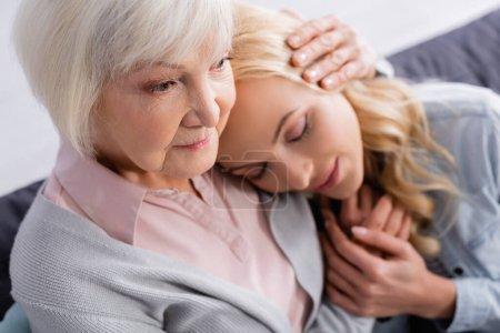 Elderly parent hugging adult daughter on blurred background