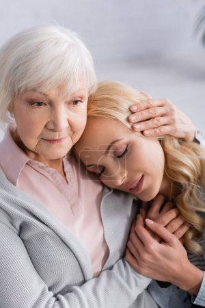 Senior woman embracing and holding hand of adult daughter
