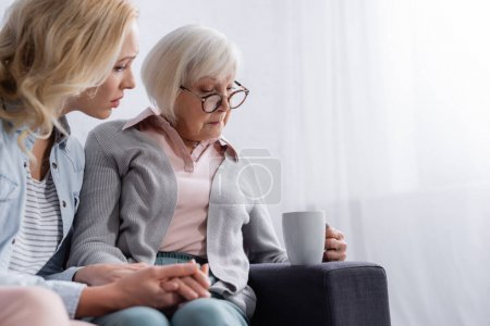 Photo for Displeased senior woman holding cup near sad daughter on blurred foreground - Royalty Free Image