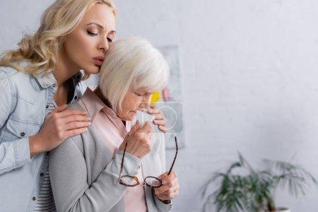 Žena uklidňující zklamaná matka s brýlemi a ubrouskem