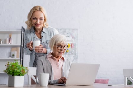 Smiling woman with cup sanding near mother using laptop