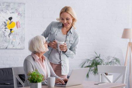 Photo pour Femme souriante tenant tasse près de la mère et gadgets sur la table - image libre de droit