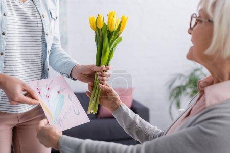 Frau überreicht Mutter Grußkarte mit 8. März-Schriftzug und Blumen im unscharfen Vordergrund
