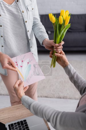 Photo for Cropped view of woman giving greeting card with 8 march lettering and flowers to parent at home - Royalty Free Image