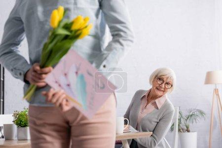Lächelnde ältere Frau neben Tochter mit Blumen und Grußkarte im verschwommenen Vordergrund