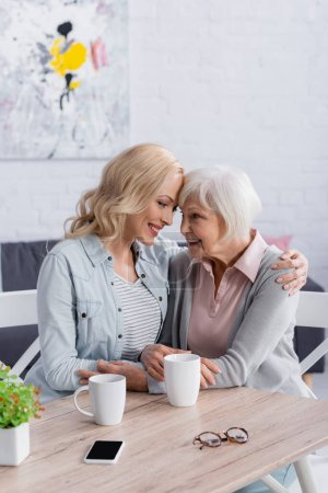 Photo for Smiling woman hugging mother near smartphone, cups and eyeglasses at home - Royalty Free Image