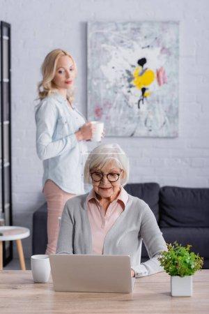 Seniorin benutzt Laptop in der Nähe von Tasse und Tochter auf verschwommenem Hintergrund zu Hause