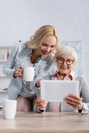 Smiling woman with cup standing near senior parent using digital tablet