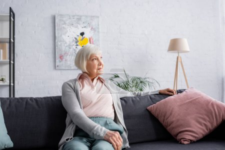 Grey haired woman looking away in living room