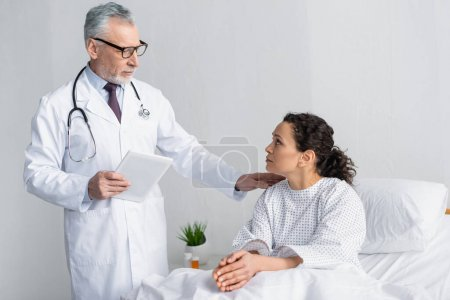 mature doctor touching shoulder of african american woman while holding digital tablet