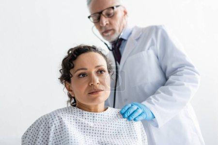 Reife Ärztin untersucht Afroamerikanerin mit Stethoskop auf verschwommenem Hintergrund