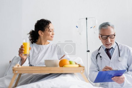 mature doctor writing on clipboard near smiling african american woman having breakfast in clinic