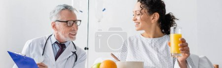 happy african american woman having breakfast near smiling doctor in hospital, banner