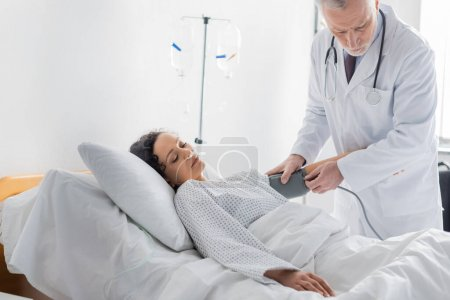 doctor measuring blood pressure of african american woman lying in hospital bed