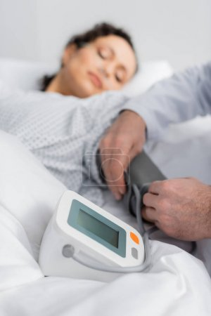 doctor measuring blood pressure of sick african american woman on blurred background