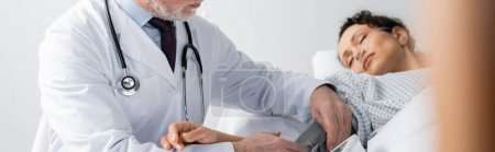 mature doctor measuring blood pressure of african american woman lying with closed eyes, banner