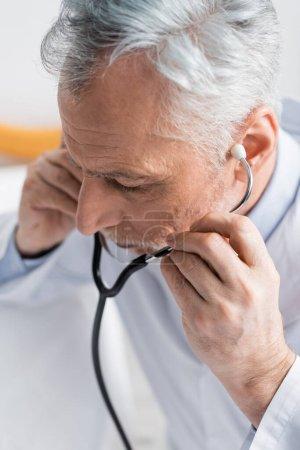 vista de ángulo alto del médico maduro que ajusta el estetoscopio en el hospital