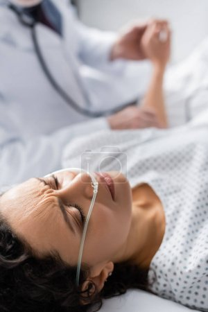 sick african american woman with nasal cannula suffering from pain near doctor on blurred background