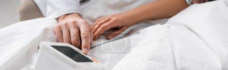 Photo pour Vue partielle du médecin mesurant la pression artérielle et le rythme cardiaque du patient, bannière - image libre de droit